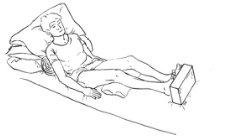 person lying in bed propped up by pillows under shoulders and legs